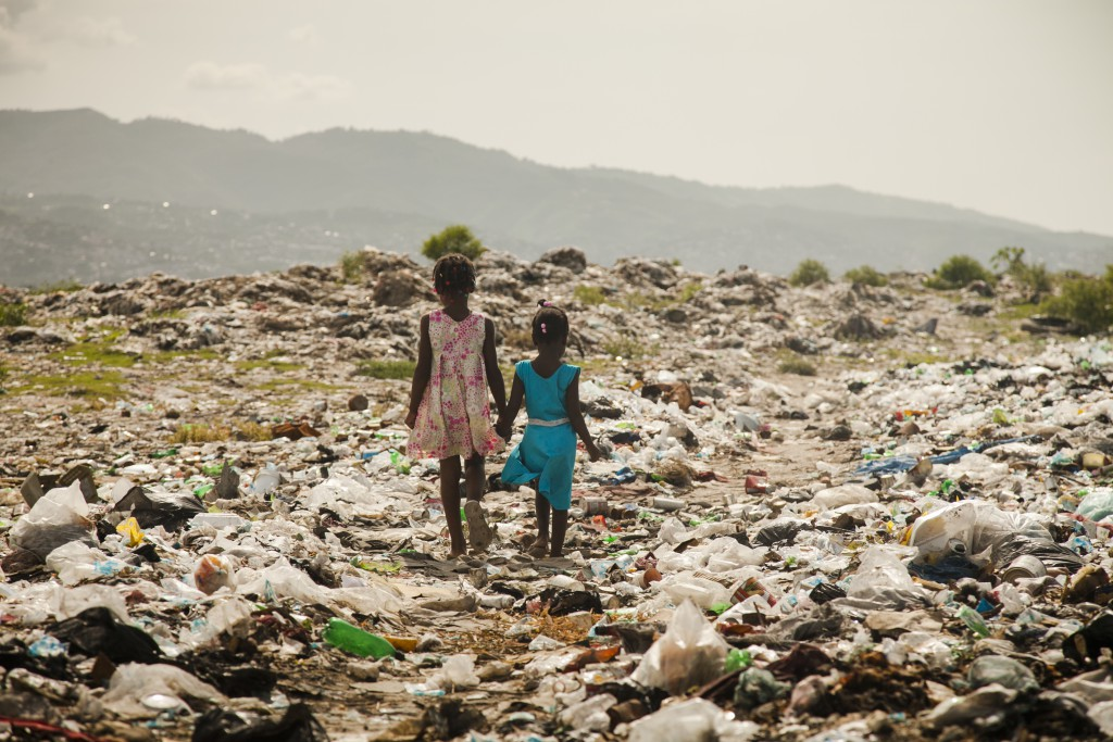 Children walking through a trash side in one of the poorest slums of the country, village de dieu. Haiti, 2010.